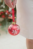 Woman holding red Christmas bauble