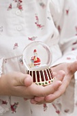 Small girl holding Christmas snow globe