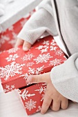 Small girl opening box with snowflake motifs