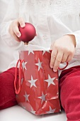 Child taking Christmas bauble out of carrier bag
