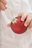 Child threading string through top of Christmas bauble