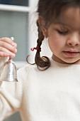 Small girl holding Christmas bell