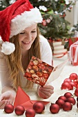 Woman in Father Christmas hat reading Christmas card