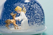 Snow globe containing deer and Christmas angel