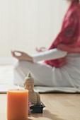 Frau im Yogasitz, Kerze und Buddhastatue
