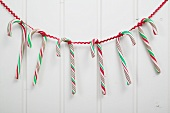Several candy canes hanging on red ribbon