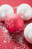 Red and white Christmas baubles with artificial snow