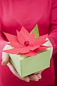 Woman holding Christmas parcel with poinsettia