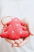 Hands holding knitted Christmas tree ornament