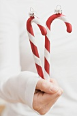 Hand holding Christmas tree ornaments (candy canes)