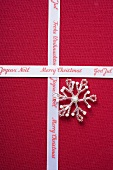 Christmas ribbon and silver star on red fabric