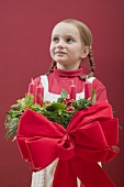 Small girl holding Advent wreath with red bow