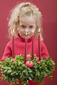 Small girl holding Advent wreath with burning candles