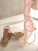 Pink bra on clothes stand, high-heeled shoes on floor