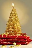 Goldfarbene Weihnachtskerze auf Servietten