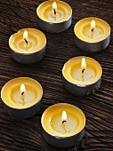 Several tealights on wooden background