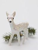 Christmas decoration (deer) in front of sprig of fir