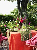 Laid table decorated with flowers and turf out of doors