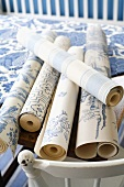 Rolls of blue and white patterned wallpaper