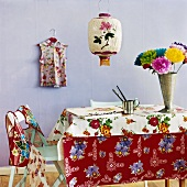 Flowers, paintbrushes & drawing pad on table, coloured tablecloth
