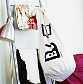 Standard lamp, clothes, magazine and laundry bag