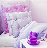 Bed with cushions & throw, cups, saucers & book on side table