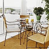Orange juice, newspaper & azalea on glass table, four chairs
