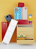 Schubladenkommode, Schränkchen, Schachteln, gestapelte Plastikdosen und Plastikkörbe vor gelber Wand
