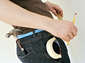 Man with hammer and sticky tape in his trouser pockets