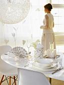 Weiss gekleidete Frau steht hinter festlich gedecktem Tisch