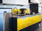Gelbe Schränke und Edelstahlfronten in moderner Küche
