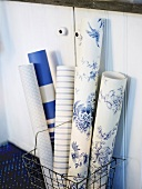 Rolls of different wallpaper in front of cupboard