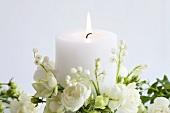 Brennende weisse Kerze mit weissen Rosen und Maiglöckchen