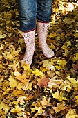Woman in rubber boots standing on autumn leaves
