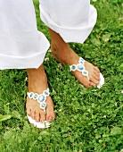 Feet in flip-flops in grass