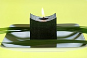 Candle and flower leaves on plate, close-up