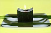 Kerze und Blätter auf Teller