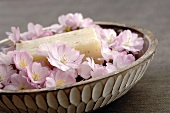 Cherry blossoms in a bowl and a bar of flavour soap, close-up