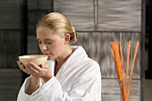 Germany, young woman holding tea bowl, close-up