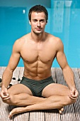 Germany, young man practicing yoga beside swimming pool, portrait