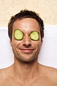Germany, young man with cucumber slices on eyes