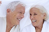 Elderly couple in bathrobes with towel