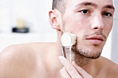 Man massaging face with brush, close-up