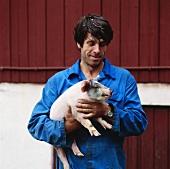Famer holding a piglet