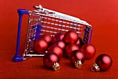 Red Christmas baubles falling out of upset shopping trolley