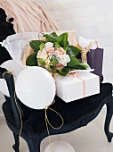 Gift, romantic bouquet and balloons in armchair