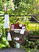 Washbasin in front of rose bush in garden