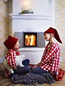 Two girls in Santa hats in front of fire