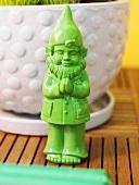 Green garden gnome in front of flowerpot