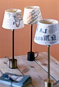 Close-up of decoupage lampshades made from newspaper, map and sheet music